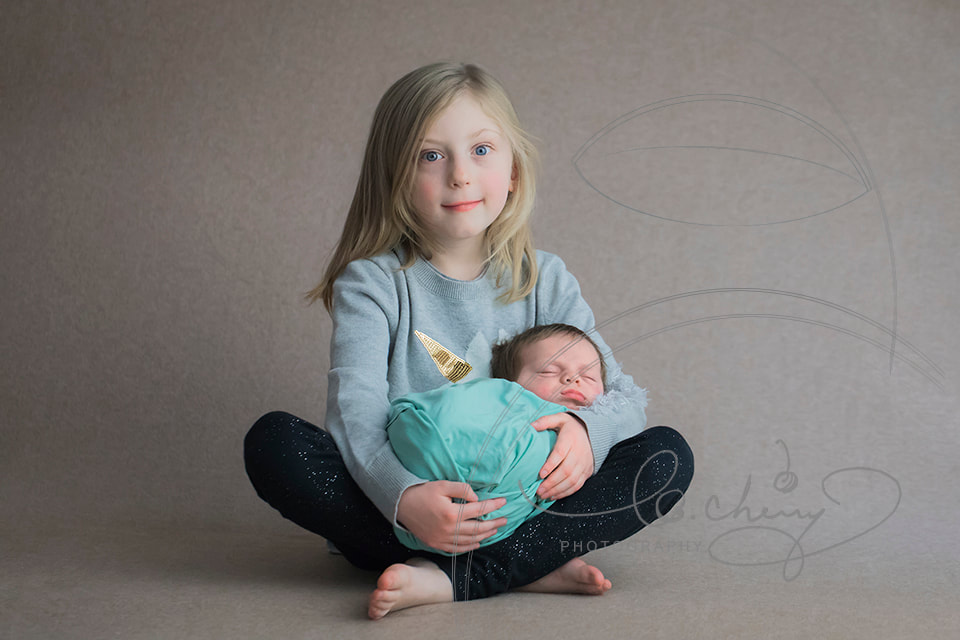 Photo of sister sitting cross-cross apple sauce holding newborn brother in her lap.