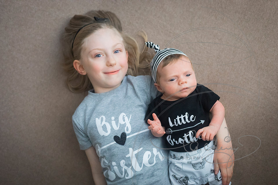 Photo of newborn boy laying next to older sister wearing little brother and big sister shirts.