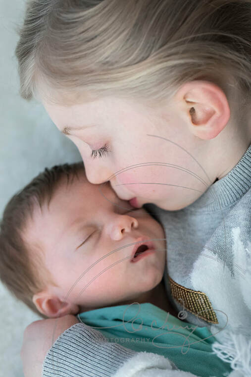 Photo of sister kissing forhead of her newborn brother.